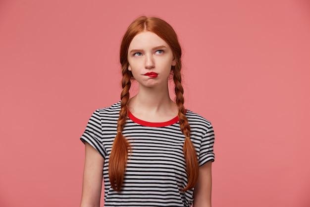 Ragazza premurosa con due trecce dai capelli rossi che morde dubbi sul labbro rosso su qualcosa, vestita con una maglietta spogliata, guarda nell'angolo in alto a destra isolato