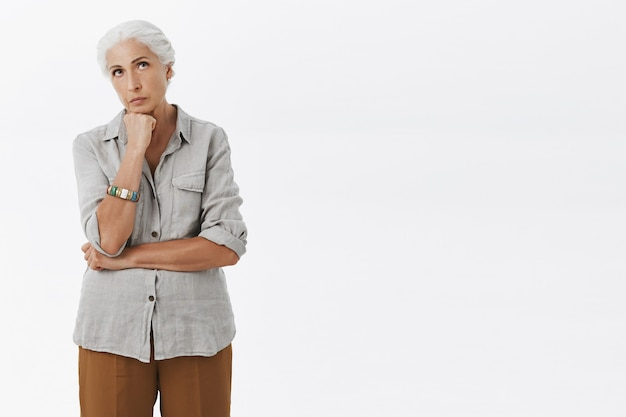 Задумчивая бабушка смотрит вверх, размышляя, белый фон