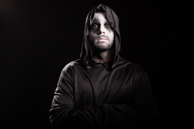 Thoughtful grim reaper over black background. spooky monster.