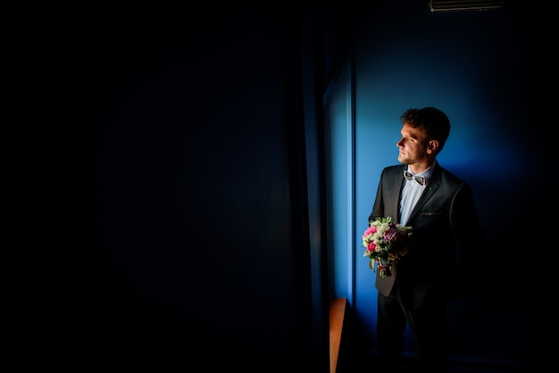 Thoughtful groom stands before a window with wedding bouquet