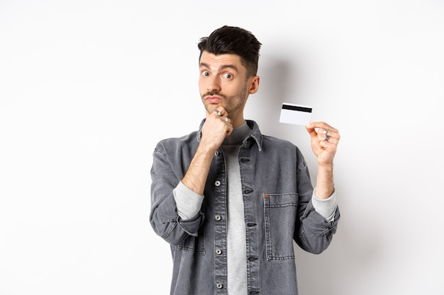 Thoughtful guy holding plastic credit card and thinking, looking intrigued at camera, touching chin while making choice, standing on white background.