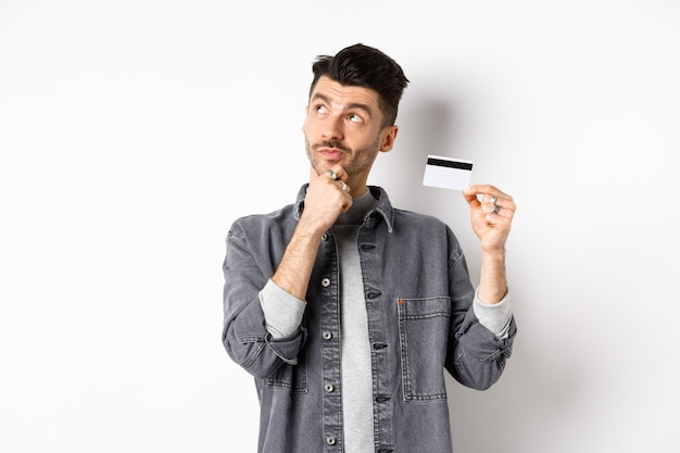 Thoughtful guy looking at upper left corner logo and holding plastic credit card, thinking about shopping, standing on white background.