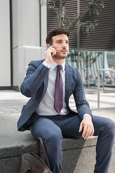 Thoughtful guy in suit talking on smartphone
