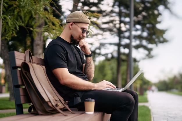 都市公園の距離の仕事でベンチに座っている間、外でリモートワークをしているラップトップを持つ思いやりのある男