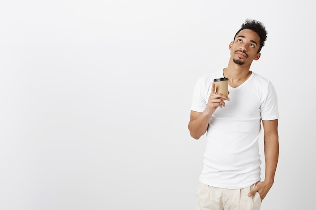 Thoughtful handsome black man in casual t-shirt looking dreamy up and drinking coffee