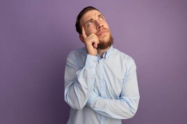 Задумчивый красивый блондин кладет палец на висок и смотрит вверх изолированно на фиолетовой стене