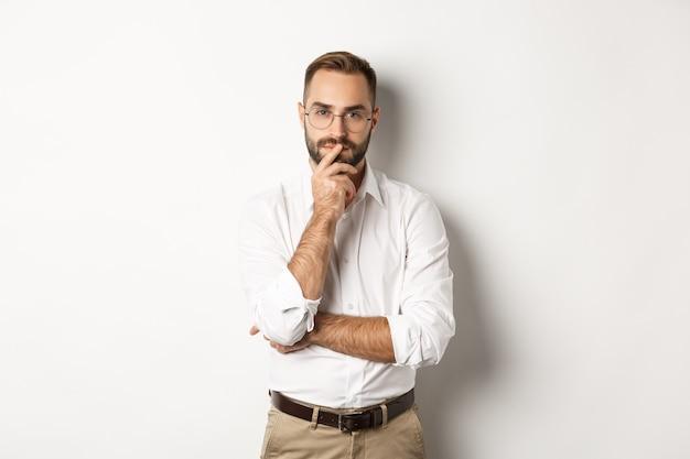 Задумчивый красивый бизнесмен смотрит в камеру, делая выбор или думая, стоя в очках и белой рубашке с воротником на фоне студии