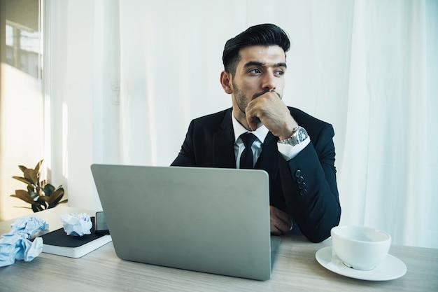 Задумчивый красивый бизнесмен думает об онлайн-проекте, глядя на ноутбук на рабочем месте