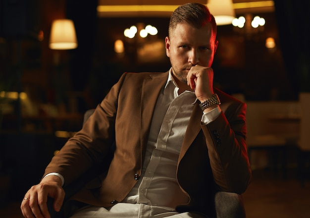 Thoughtful handsome businessman wearing suit posing in restaurant