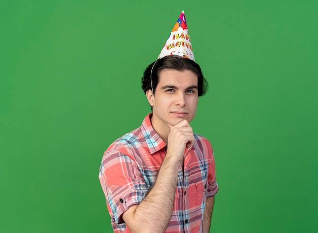 L'uomo caucasico bello premuroso che indossa il berretto di compleanno tiene il mento