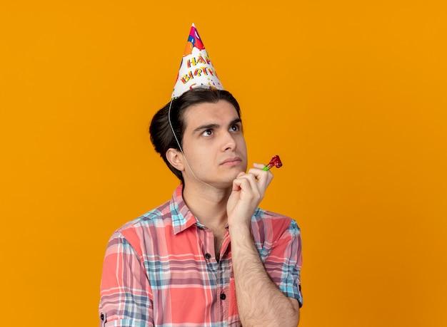 생일 모자를 쓰고 사려 깊은 잘 생긴 백인 남자가 측면을보고 파티 휘파람을 들고 턱에 손을 넣습니다.
