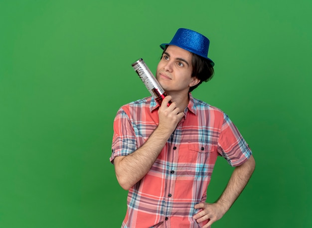 Thoughtful handsome caucasian man wearing blue party hat holds confetti cannon looking at side