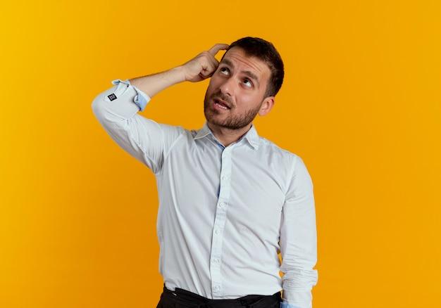 Uomo bello premuroso mette il dito sulla testa guardando in alto isolato sulla parete arancione