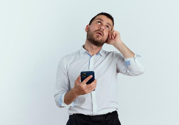 Riflessivo bell'uomo mette la mano sul tempio tenendo il telefono e guarda in alto isolato sul muro bianco