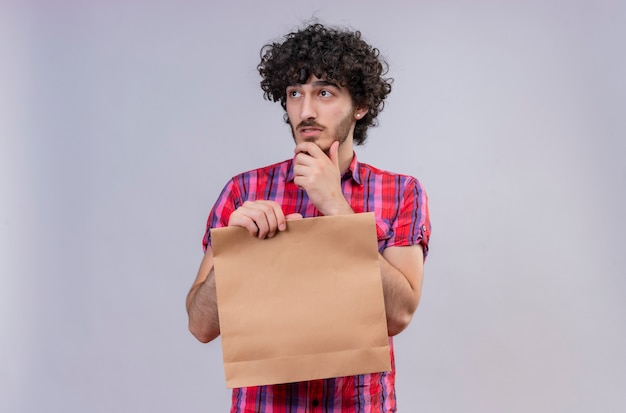 A thoughtful handsome man with curly hair in checked shirt holding shopping bag looking at the side