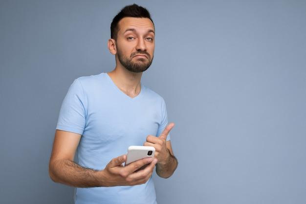 思いやりのあるハンサムな若い男は、携帯電話を保持し、使用して日常の服を着て背景の壁に隔離