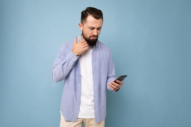 Задумчивый красивый молодой человек изолирован над стеной в повседневной одежде, держащей и использующей мобильный телефон, написание sms, глядя вниз и думая.