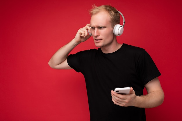 思いやりのあるハンサムな若い男が壁の壁を越えて孤立し、日常の服を着て携帯電話を持って横を向いて考えているsmsを書いています。