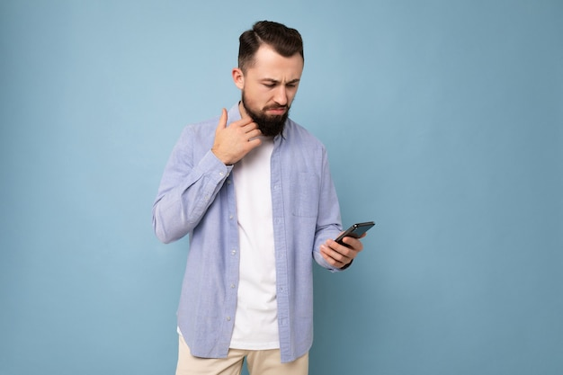 Thoughtful handsome young man isolated over wall wall wearing everyday clothes holding and using mobile phone writing sms looking down and thinking.