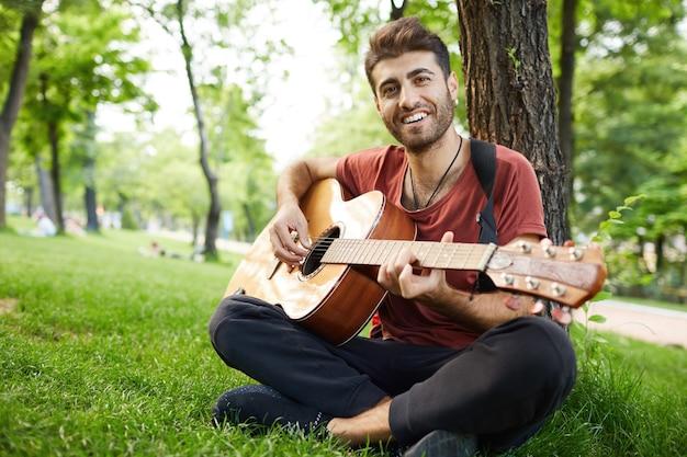 Задумчивый красивый молодой человек играет на гитаре в парке, опираясь на дерево и сидит на траве