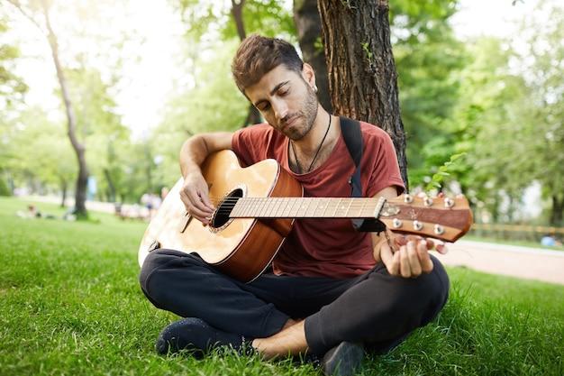 思いやりのあるハンサムな若い男が公園でギターを弾き、木にもたれて草の上に座る