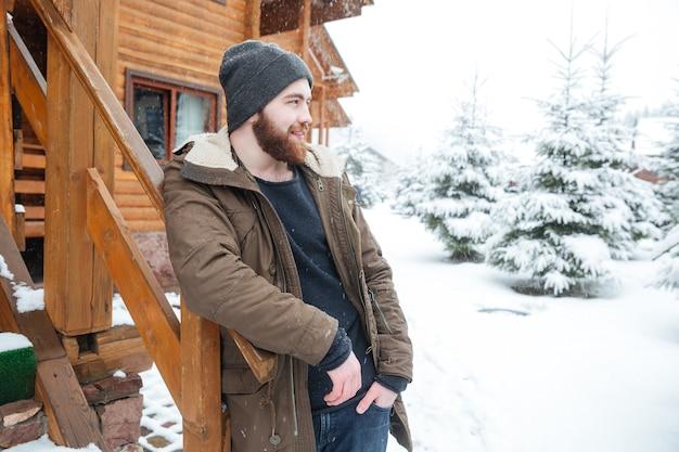 Задумчивый красивый молодой человек с бородой стоит возле бревенчатой хижины зимой