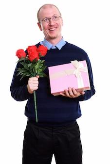 Задумчивый счастливый человек улыбается, держа красные розы и подарочную коробку