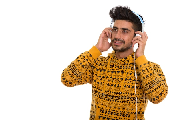 Thoughtful happy persian man smiling while listening to music an