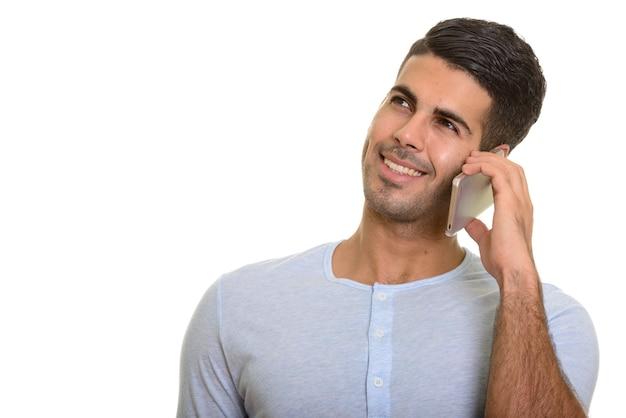 Задумчивый счастливый персидский мужчина улыбается во время разговора по мобильному телефону