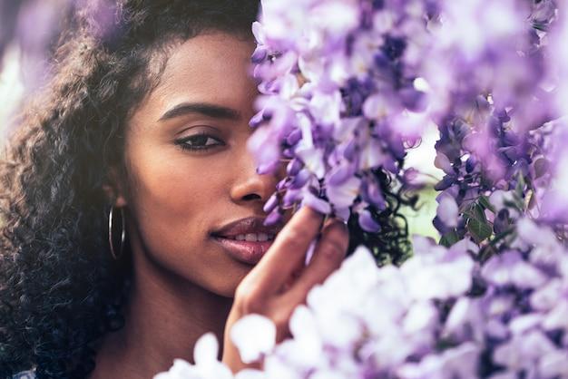 Вдумчивый счастливая молодая негритянка в окружении цветов