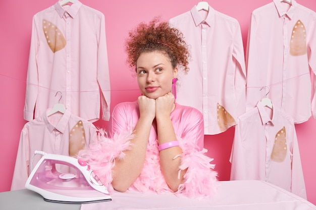 Thoughtful hard working housewife leans elbows on ironing board contemplates about something wears silk gown daydreams about having rest with family poses in laundry room clothes on hangers around