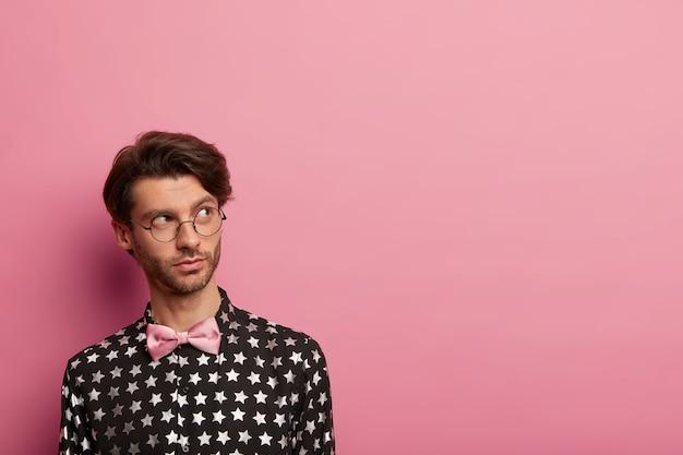 Premuroso hipster in camicia nera alla moda e papillon rosa, pronto per un appuntamento con la ragazza, pensa a cosa regalare, indossa occhiali rotondi