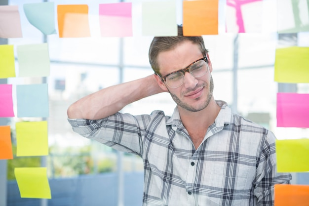 Thoughtful hipster man with post-it in office