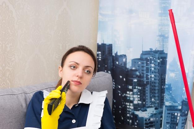 窓の前に座っている高層マンションの思いやりのある家政婦。携帯電話を手に、街の屋根を眺めることができます。