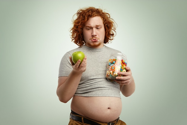 Thoughtful indecisive redhead overweight fat man with big stomach feeling confused and hesitant, facing difficult choice: whether to eat healthy organic apple or unhealthy sweets