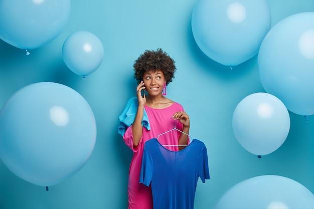 사려 깊은 우유부단 한 여성은 친구와 전화로 대화를 나누고, 옷을 입고 사진을 찍고, 옷걸이에 파란 드레스를 들고 있습니다. 매혹적인 소녀 쇼핑 중독, 옷을 사고 풍선 위에 포즈