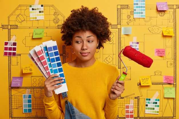 Thoughtful indecisive woman looks at color samples, holds paint roller, thinks about refurbishment of walls in new house, poses against sketch with sticky written notes. repair, building, home concept