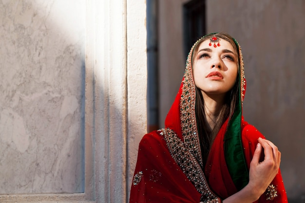 Thoughtful indian bride covered with red sari