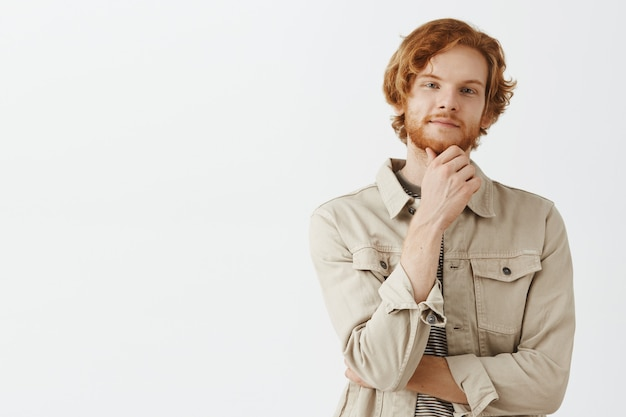 Ragazzo dai capelli rossi barbuto premuroso e incuriosito in posa contro il muro bianco