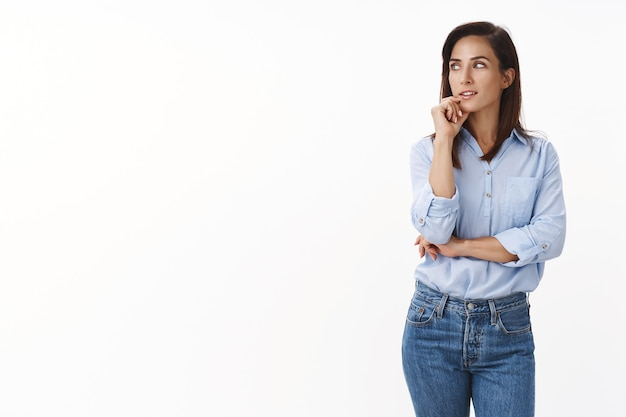 사려깊은 호기심 많은 백인 성인 여성 기업가는 흥미로운 생각을 하고, 관심을 갖고 고민하고, 턱을 만지고, 영감을 찾고, 생각을 갖고, 흰 벽에 서 있습니다.
