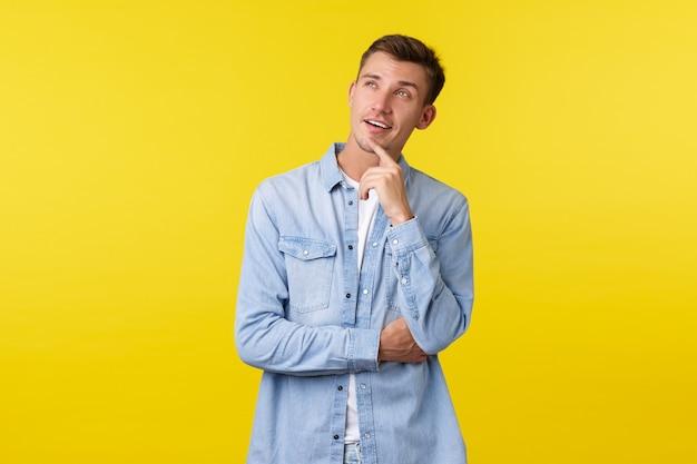 思慮深く興味をそそられるハンサムな金髪の男が店で選択をし、左上隅を好奇心旺盛に見て、あごに触れ、棚で商品を選んで目を細め、黄色の背景に立っています。