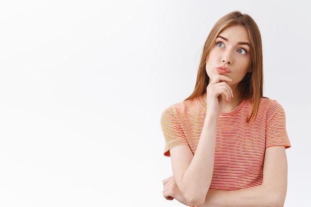 縞模様のtシャツを着た思慮深い興味をそそる若い金髪の少女、あごに触れて好奇心旺盛なふくれっ面、左上隅を見て興味をそそられ、確信が持てず、選択をし、決定を考え、白い背景