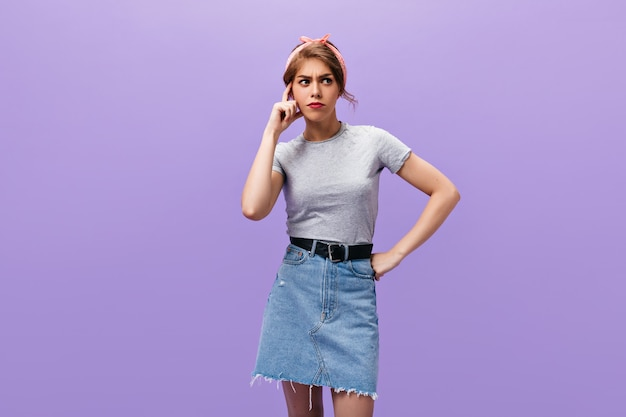 Thoughtful lady in denim skirt poses on isolated background. stylish young woman in pink headband and light shirt looking away.