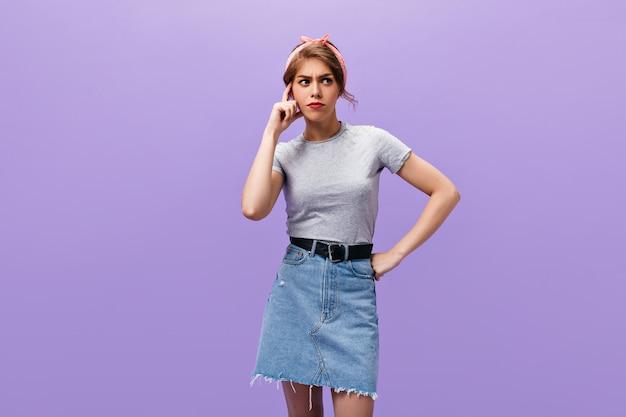 デニムスカートの思いやりのある女性は、孤立した背景にポーズをとる。ピンクのヘッドバンドと薄手のシャツを着たスタイリッシュな若い女性が目をそらしています。