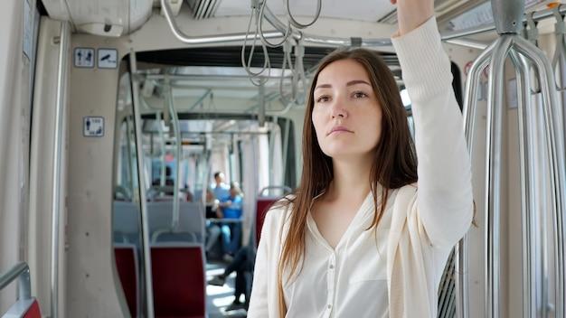 Задумчивая дама в белой одежде стоит в вагоне трамвая и держит повязку на поручнях, направляясь к центру города крупным планом