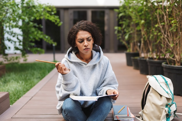 Thoughtful lady with dark curly hair sitting with book on knees and pencil in hand while sadly