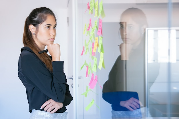 Thoughtful latin businesswoman holding marker and reading notes on glass wall. focused confident pretty female worker in suit thinking about idea for project.