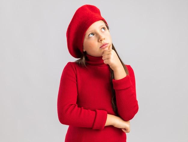 Premurosa bambina bionda che indossa un berretto rosso che guarda in alto tenendo la mano sul mento isolato sul muro bianco con spazio di copia