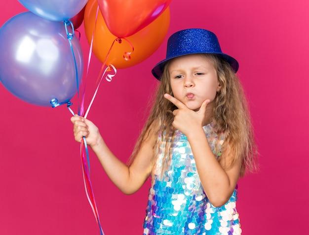 Premurosa bambina bionda con cappello da festa blu che mette la mano sul mento e che tiene palloncini di elio isolati sulla parete rosa con lo spazio della copia