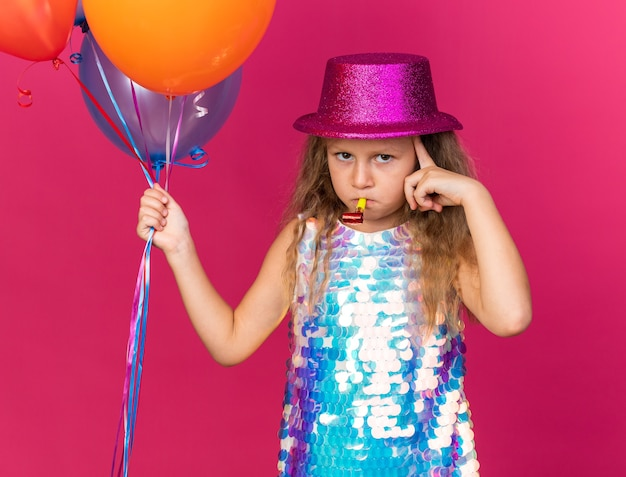 Thoughtful little blonde girl with purple party hat holding helium balloons and blowing party whistle isolated on pink wall with copy space